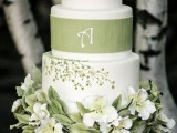 a rustic spring wedding cake with white and green botanical tiers, a white tier with green ribbon and faux blooms