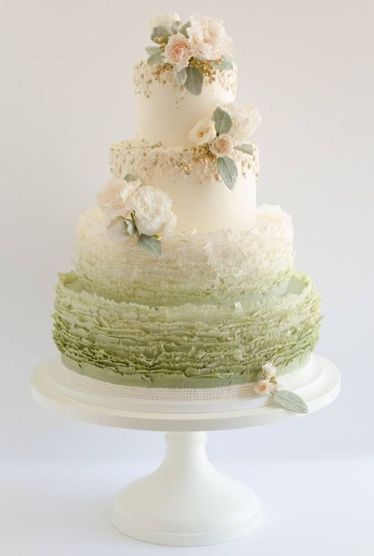 a white and ombre green wedding cake with ruffles, white and blush blooms and pale leaves is refined and chic