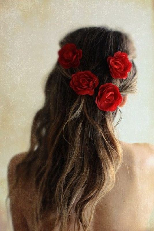 a messy half updo accented with red roses is a beautiful and very chic idea for a modern and romantic Valentine's Day bride
