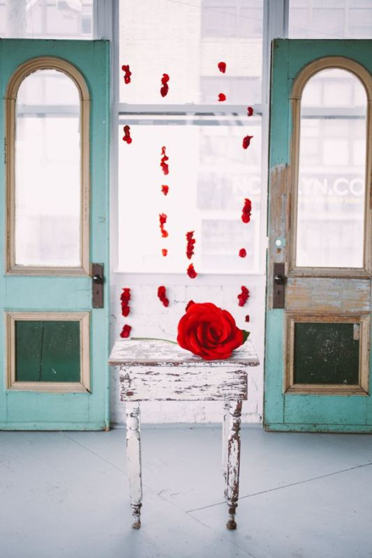 an oversized red rose instead of a large wedding bouquet and some red petals hanging down to decorate the altar or the venue are a beautiful and classic idea