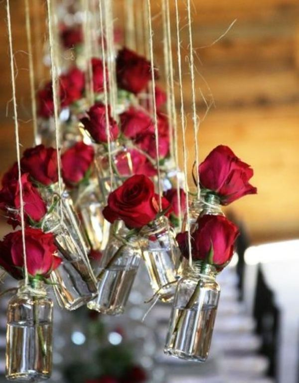 red roses hanging in bottles over the space will be a beautiful and a bit rustic decoration for a modern Valentine's Day wedding
