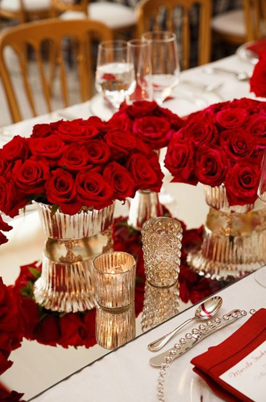 a lush red rose centerpiece in metallic vases and with candles is a very refined and chic idea for a Valentine's Day wedding