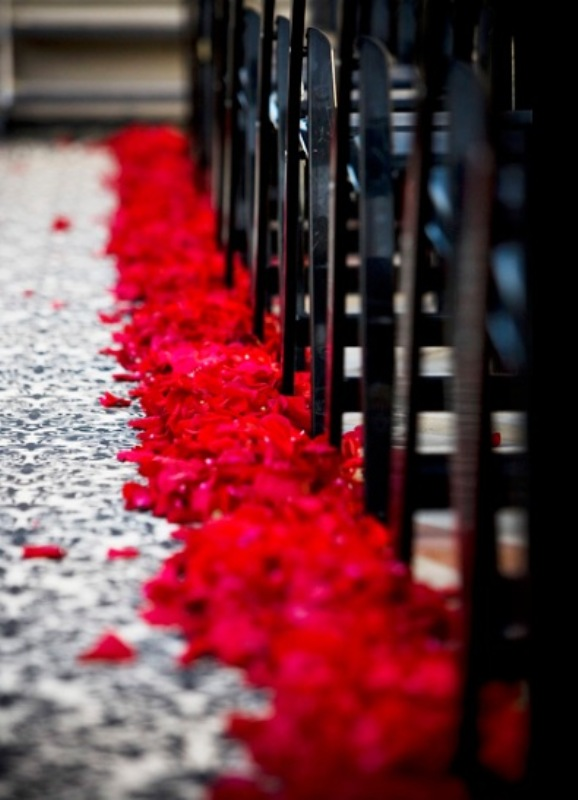 decorate your wedding aisle with red rose petals to make it look chic and adorable and infuse the space with romance
