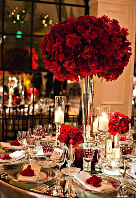 a lovely red rose wedding centerpiece of several lush arrangements and with red roses to mark each place setting is a beautiful idea