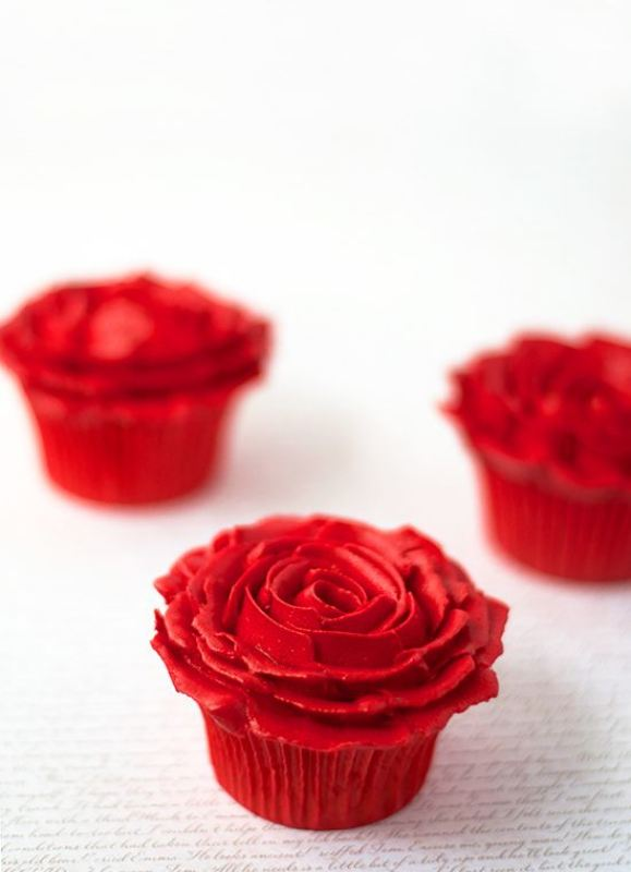 red cupcakes with red frosting that forms a rose on top are lovely for a Valentine's Day wedding