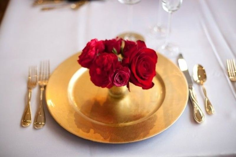 a red rose arrangement placed into a gold vase, with a gold charger and cutlery looks very romantic and very glam like