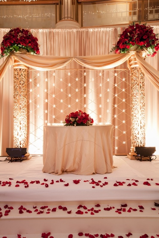 lush red rose arrangements on the table and over it for a beautiful and very refined Valentine's Day wedding look