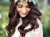the bride wearing a neutral lace wedding dress and a green leafy crown for a boho chic look