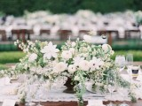 a beautiful and large textural wedding centerpiece of greenery and white blooms is a chic idea for a spring or summer wedding
