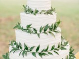 a white textural buttercream wedding cake decorated with greenery is a cool idea for every neutral wedding