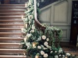 beautiful wedding staircase decor with greenery and white blooms plus multiple candles in candleholders