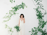 a wedding backdrop – a white brick wall and greenery branches attached in a whimsy way