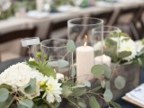a simple wedding centerpiece of a wooden box, greenery and white blooms and candles