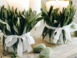 white candles wrapped with greenery and with white bows for a chic and organic look