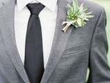 a simple greenery and white bloom boutonniere refreshes the simple groom's look in grey and black