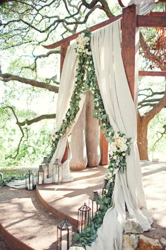 a beautiful ceremony space with neutral curtains decorated with greenery and white blooms and with candle lanterns