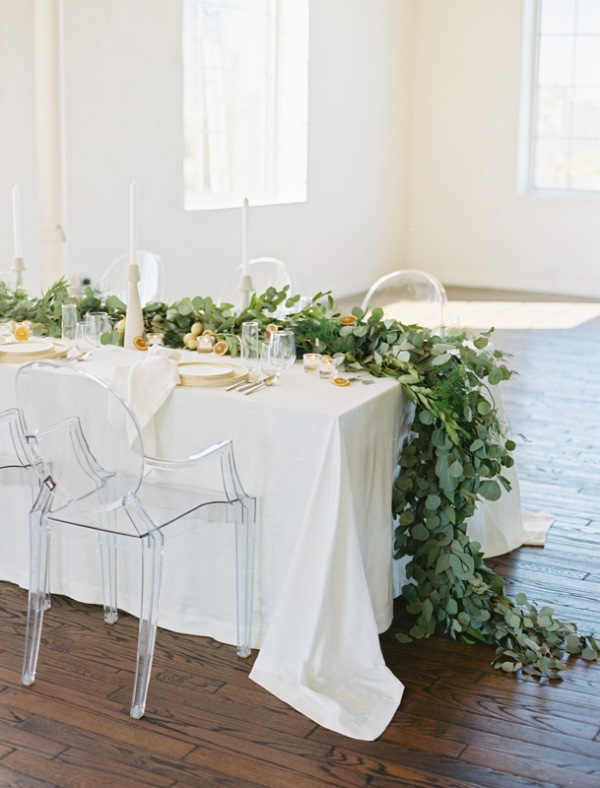a chic wedding tablescape with greenery table runners, citrus, gilded touches and a neutral tablecloth