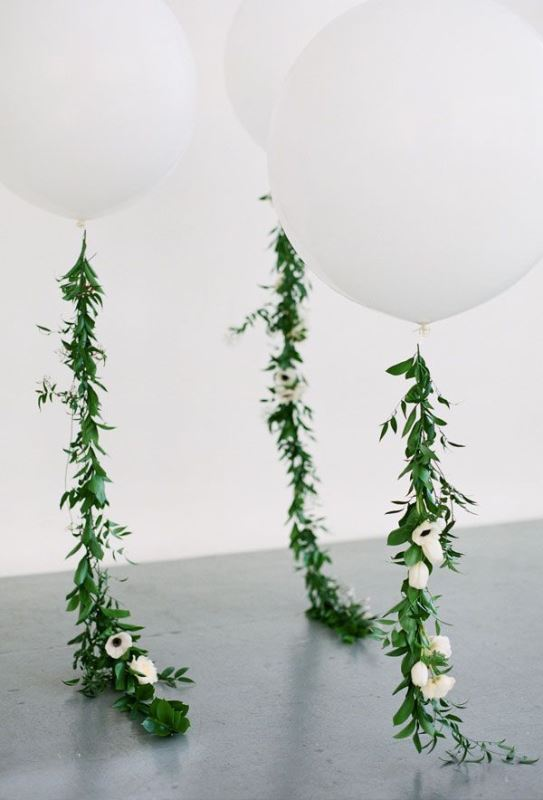 giant white balloons with greenery and white blooms are amazing for modern wedding decor