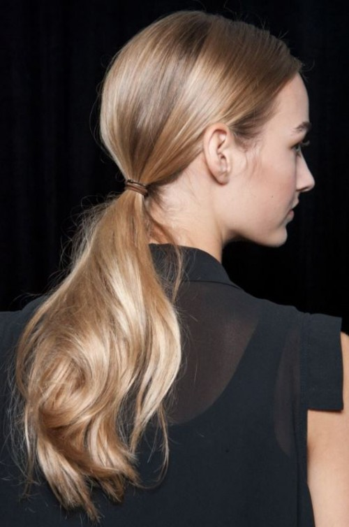 a low ponytail with a sleek top and a wavy pony is a stylish and fast to realize idea