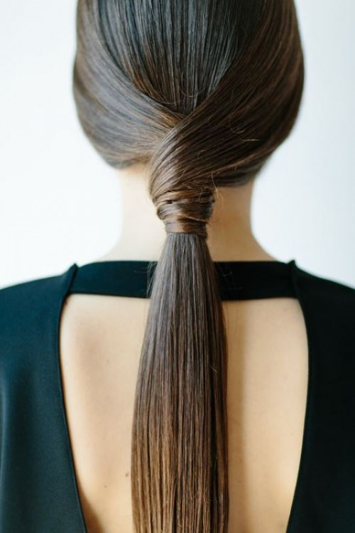 a sleek twisted low ponytail is a stylish idea for a modern or minimalist bride