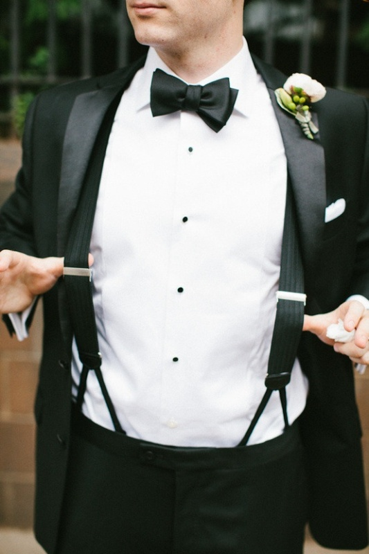 a classic black tux worn with black suspdenders is a stylish idea for a modern and refined groom