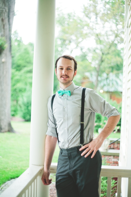 black pants, black suspenders, a grey shirt and a turquoise bow tie for a stylish groom's look with a touch of color
