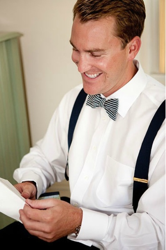 black pants, black suspenders, a white shirt, a striped bow tie for a modern and bold look