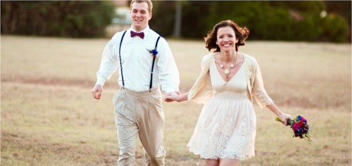 neutral pants, a white shirt, black suspenders and a burgundy bow tie for a chic and simple groom's look