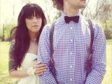 a blue plaid shirt, grey suspenders and a black bow tie plus black jeans for a rustic spring groom's look
