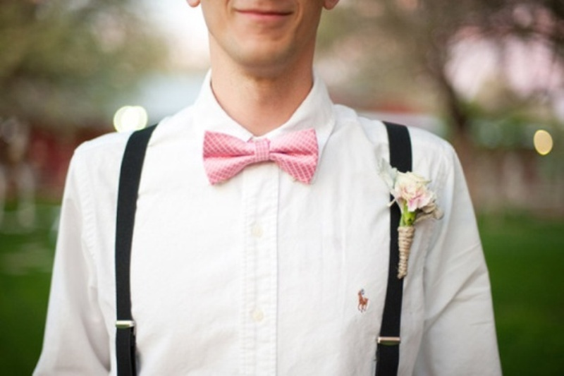 a white shirt, black suspenders, a pink bow tie and a blush floral boutonniere for an elegant summer groom's look