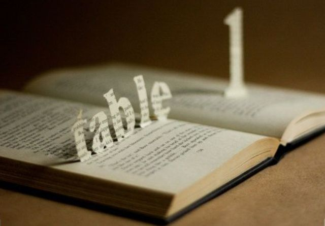 a vintage book with table 1 cut out right in it   just add some greenery or blooms and voila