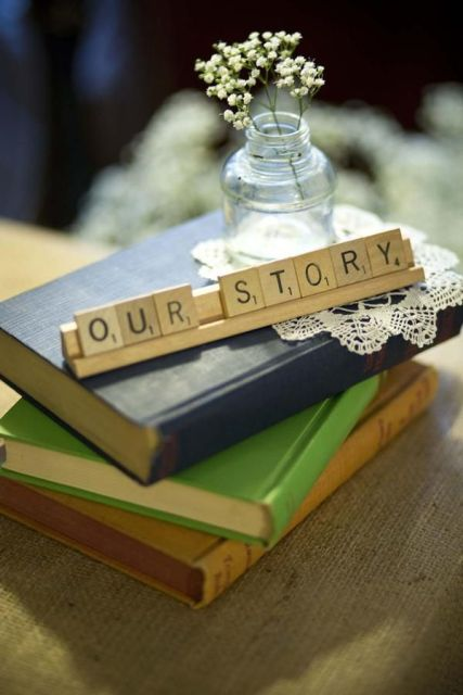 a stack fo vintage books with scrabble letters, a doily and some baby's breath in a bottle