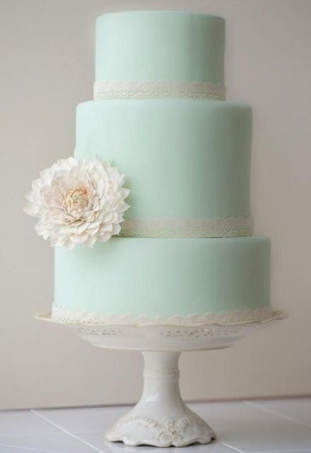 a chic mint green wedding cake with white lace ribbons, a single white bloom on a stylish and refined stand