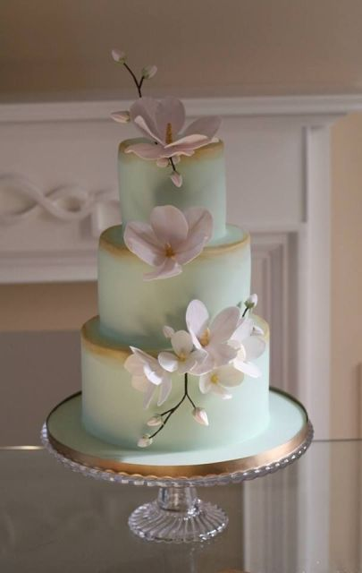 a refined mint green wedding cake with gold edges and luxurious white sugar blooms on a chic stand