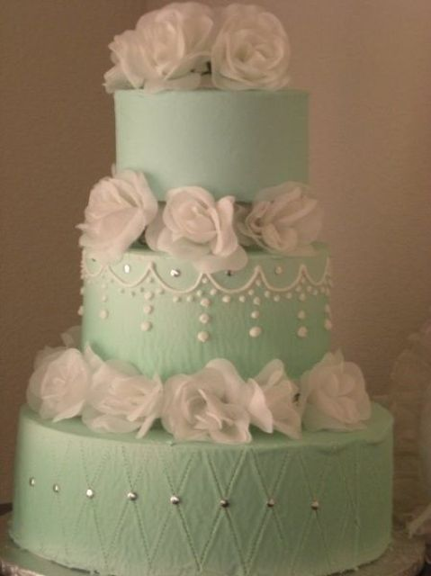 a bold mint green wedding cake with white sugar blooms and edible beads is a stylish idea