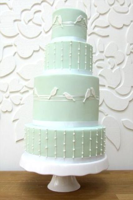 a cute pastel green wedding cake decorated with white beads and birds on its sides for a spring wedding