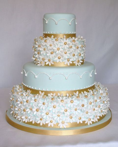 a beautiful mint green wedding cake with patterned tiers and floral ones plus gold decor is a statement idea