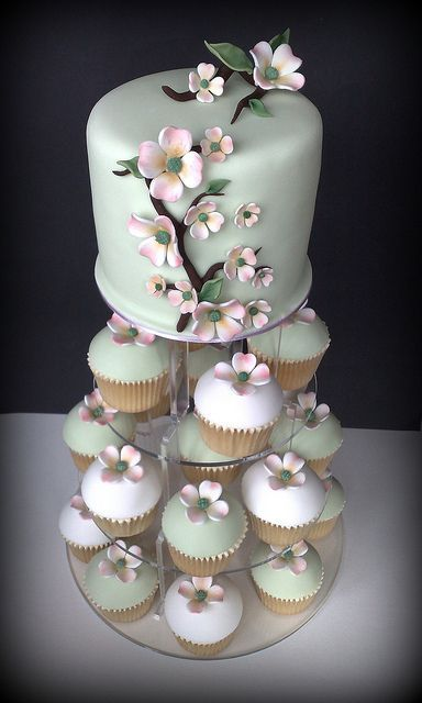 a whimsy mint green wedding cake decorated with pink sugar blooms and matching cupcakes for a chic dessert table