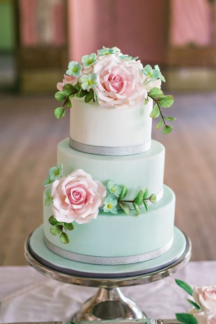 an ombre mint green wedding cake with shiny ribbons and sugar greenery and blooms and two pink flowers