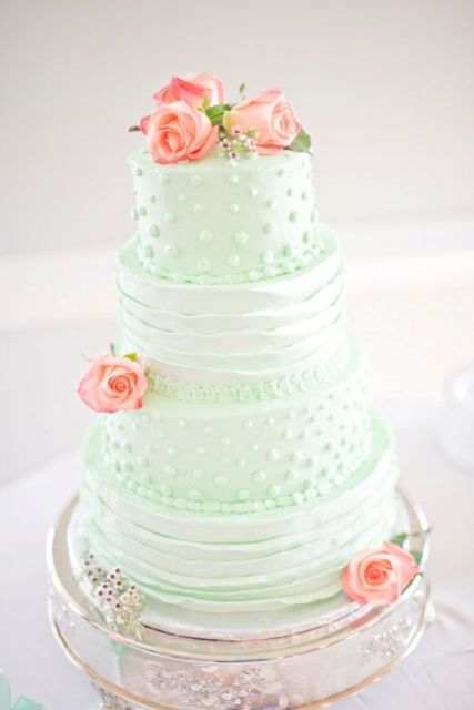 a whimsy mint green wedding cake decorated with ruffles and polka dots and fresh pink blooms here and there