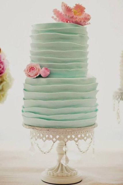 a tiered and ruffled mint green wedding cake topped with pink sugar blooms for a spring or summer wedding