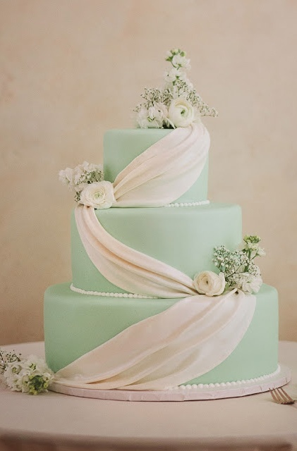a formal mint green wedding cake decorated with edible white ribbon and fresh blooms and greenery