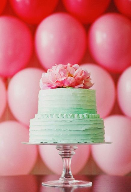 a romantic ombre mint green wedding cake topped with bold pink blooms for a summer wedding