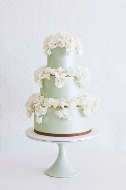 a luxurious mint green wedding cake topped with lots of white sugar blooms