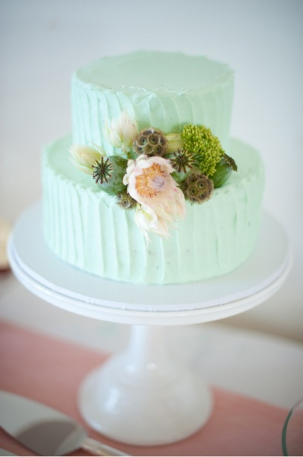 a casual textural buttercream mint green wedding cake with blooms, greenery and moss