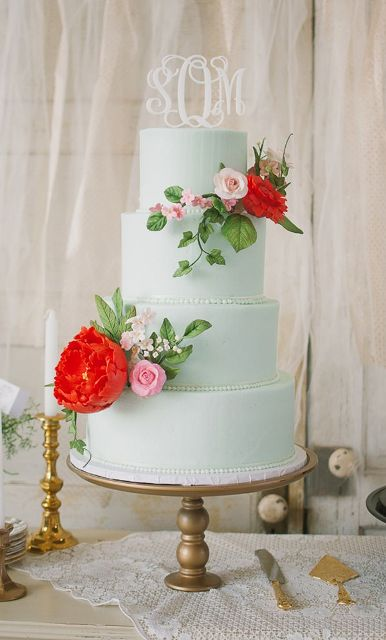 an elegant mint green wedding cake with pink and red fresh flowers and a monogram on top