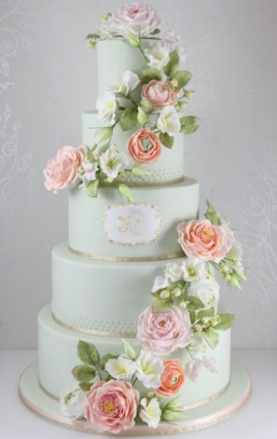a romantic mint green wedding cake with shiny ribbon, a monogram and fresh peachy and white blooms and greenery