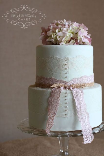 a mint green wedding cake decorated with white and pink lace and fresh pink hydrangeas on top