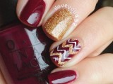 burgundy nails with gold glitter accents and a bold chevron nail for a more outstanding look