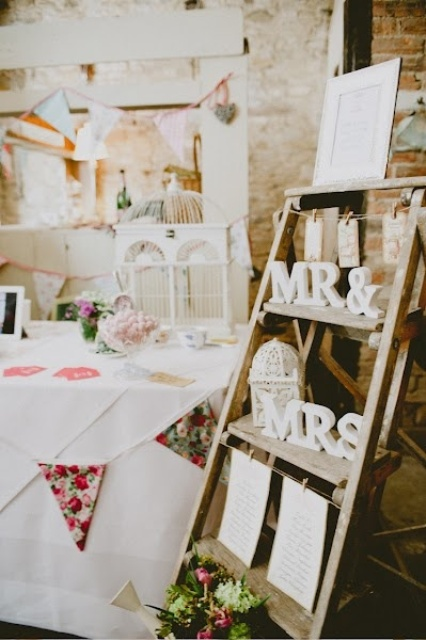 a wedding seating chart of a wooden ladder, some letters, a cage, a bunting, a seatign plan and some blooms